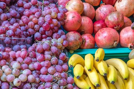 edibles: Pomegranates, bananas and grapes for sale at a market