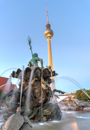 The Neptune fountain and the TV Tower in Berlin at twilight Editorial
