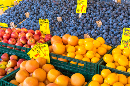 edibles: Plums, apples and oranges for sale at a market Stock Photo