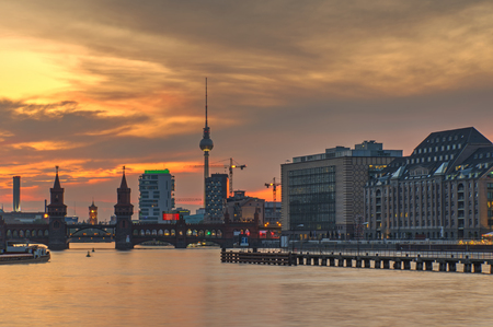 or spree: Fire in the sky over Berlin with the famous television tower and the river Spree