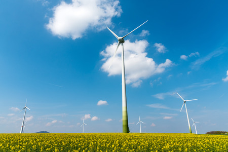 Windmill-powered plant and rapeseed field seen in Germany Stock Photo