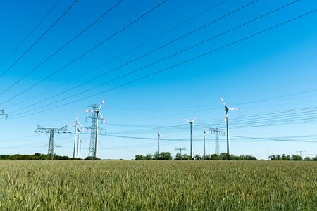 Wind power plants and power transmission lines lakes in rural Germany Reklamní fotografie