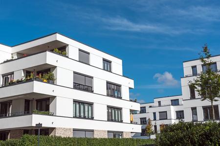 Nuevas casas blancas frente a un lago de cielo azul en Berlín, Alemania