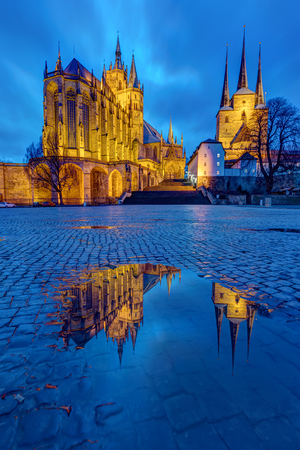 The famous Cathedral and Severi church at Erfurt at dusk reflected in a puddle Stock Photo