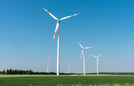 Wind power generators in front of a clear blue sky lake in Germany