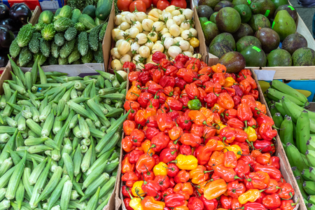 Mini bell peppers, pickles and peas for sale at a market Stock Photo