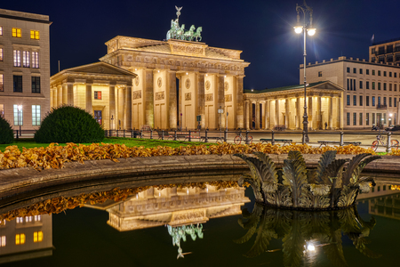 The famous Brandenburg Gate in Berlin at night, reflected in a fountain