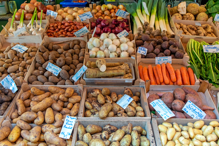 Different types of potatoes and other vegetables for sale at a market Editorial