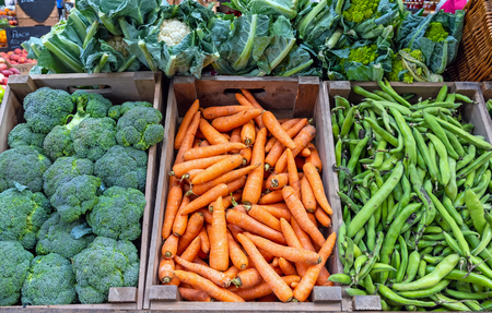 Broccoli, carrots and green peas for sale at a market