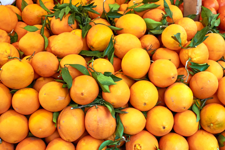 Fresh ripe clementines with green leaves for sale at market