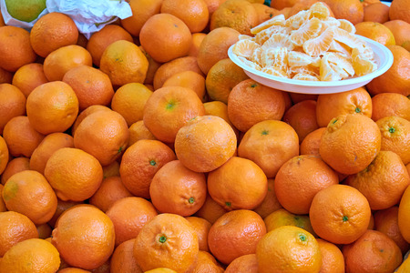 Tangerines for sale at a market with some pieces on a plate Stock Photo
