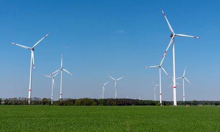 Wind power plants, green fields and blue skies lakes in rural Germany