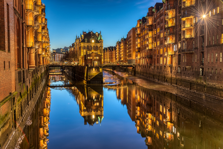 The old Speicherstadt with the moated castle in Hamburg, Germany, at twilight Stock Photo