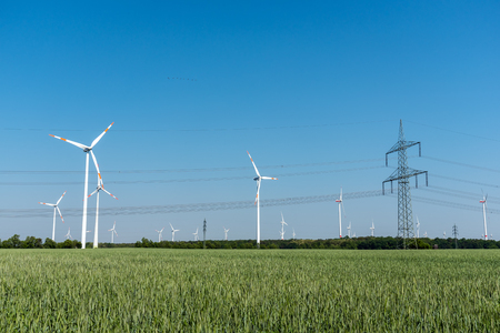 Wind turbines and overhead power line in Germany Stock Photo