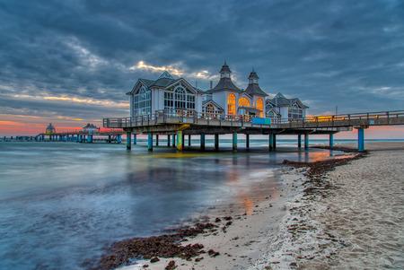 The sea pier of Sellin on Ruegen island in Germany with dark clouds before sunrise