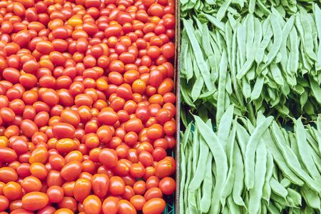 Small tomatoes and green beans for sale at a market
