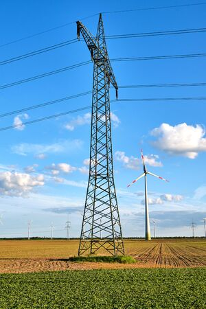 An electricity pylon with wind energy generators in the back seen in Germany