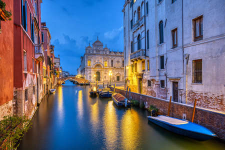 Canal in the old town of Venice at dusk with the Scuola Grande di San Marco in the back