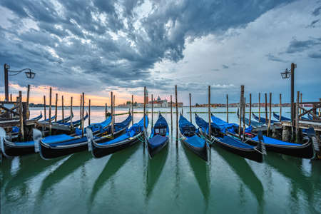 Gondolas at the St. Marks square in Venice, Italy, before a dramatic sunrise