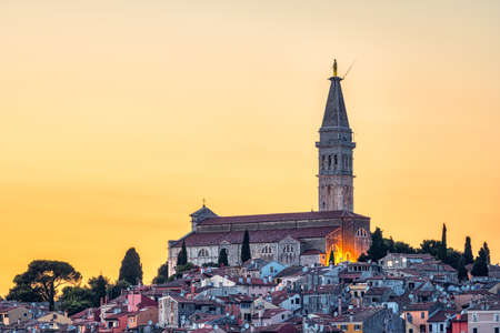 The old town of Rovinj in Croatia with the iconic Saint Euphemia church at sunset Imagens
