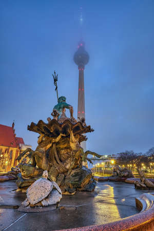 Foggy autumn morning at the Television Tower and the Neptune fountain at Alexanderplatz in Berlin Imagens