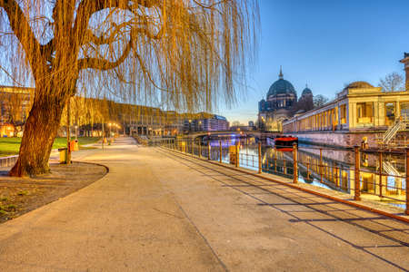 Footpath with a weeping willow tree at the Museum Island in Berlin before sunrise Imagens