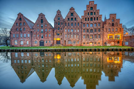 The historic Salzspeicher reflecting in the Trave river at dawn, seen in Luebeck, Germany Imagens
