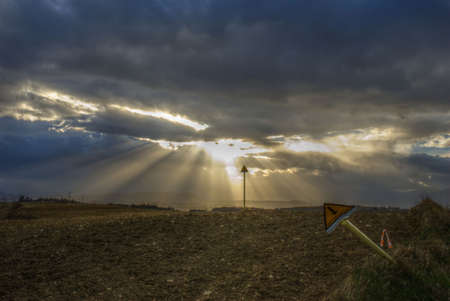 methane: Hdr immage: sun beams bursting through very dark threatening clouds over the methane tubes sign posts(metanodotto is not a trademark, it just means methane tubes) Stock Photo