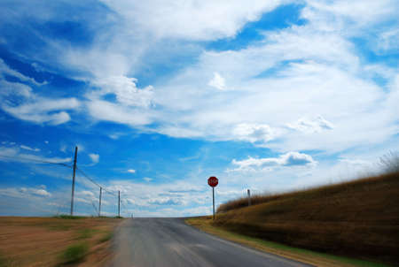 motion blurred road going toward the stop under cloudy blue sky Stock Photo