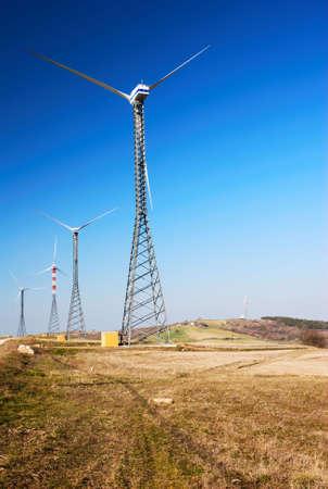 Wind turbines in a field under clear blue sky Stock Photo - 3028824