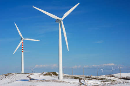 Modern and ecologic wind turbines with blue sky and snowy hill Stock Photo - 4408384