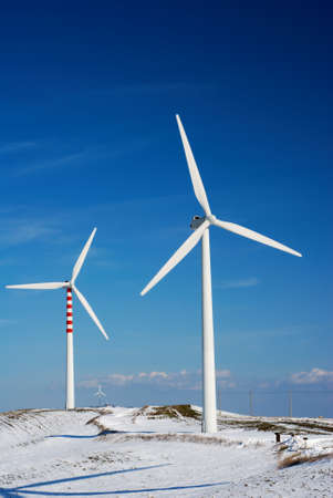 Modern and ecologic wind turbines with blue sky and snowy hill Stock Photo - 4434169