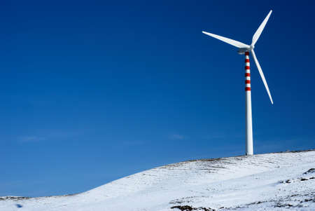 Modern and ecologic wind turbine with blue sky and snowy hill Stock Photo - 4461162