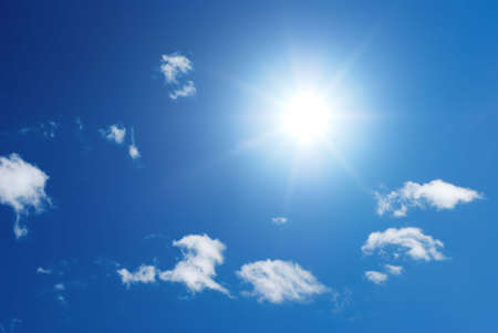 clearness: Sung in a blue sky with little white puffy clouds Stock Photo