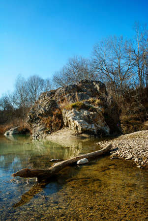 View of river Biferno with trunk in shallow water (Molise, center Italy)