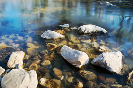 Irregular stones in the shallow water of riverside with sky reflection photo