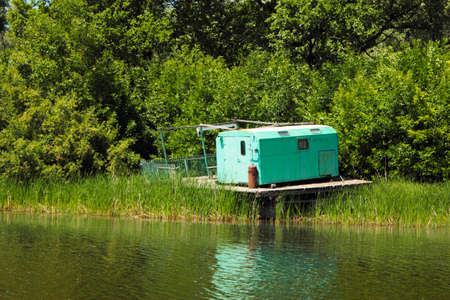 green barn on a water platform on the river bank Stok Fotoğraf