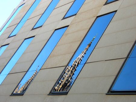 modern building in barcelona with cathedral reflected. Mix of new and old buildings