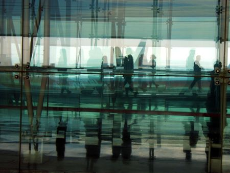 many people walking from one place to another in an airport Stock Photo