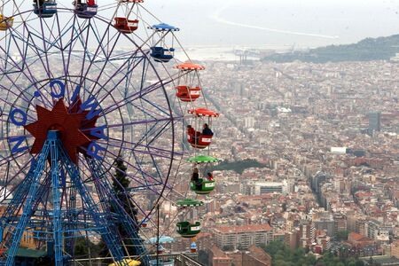 colorful funfair wheel against cityscape Stock Photo