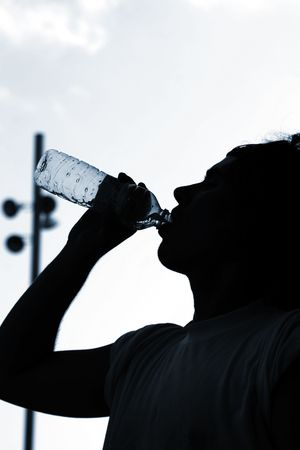 a thirsty boy is drinking water after match. With copyspace