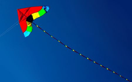 kite in red yellow and green against intense blue sky. With space for text