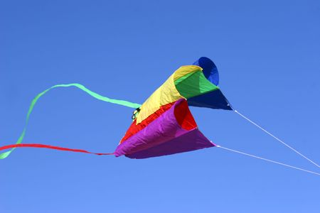 flying kite: kite in red yellow and green against intense blue sky. With space for text