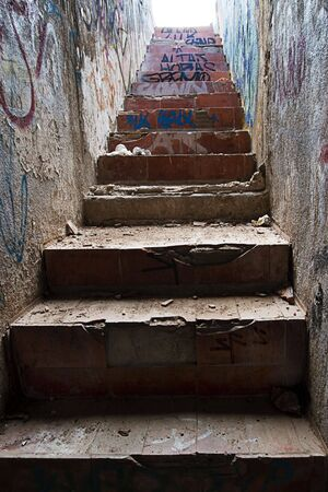 Old stairs, partially ruined and very dirty. Almost everything covered with graffiti. photo