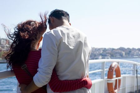 embracing Young loving couple enjoying a cruise . Strong hair movement due to the wind