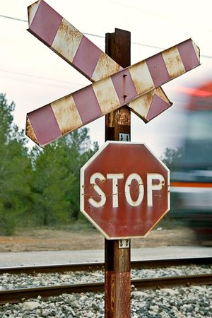 Railway stop sign with train movement blur off to the right.  photo