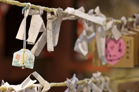 A view of written cards and notes with the desires and wishes of people attached to a rope in a Buddhist temple. Stock Photo