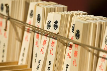 A view of written cards tables with good luck desires attached to a rope in a Buddhist temple. Stock Photo