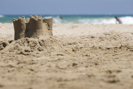 Small sand castle on the beach with ocean in the background. Stock Photo