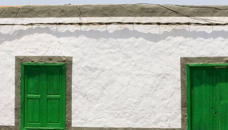 old window and door in green wood. Textured wall with copyspace. Beautiful shadows
